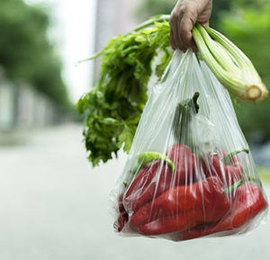 woman taking a bag of vegetables walking on road